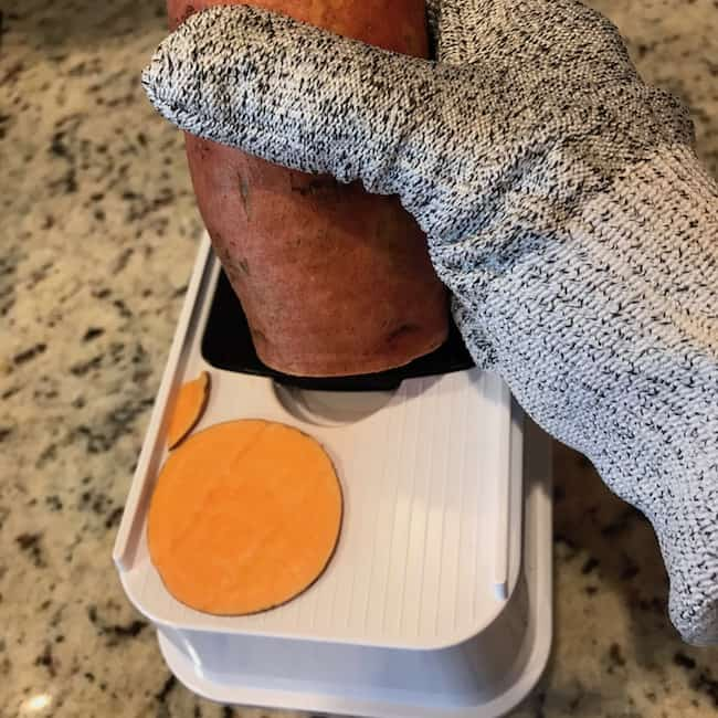 Slicing sweet potato with a mandolin while wearing a protective glove