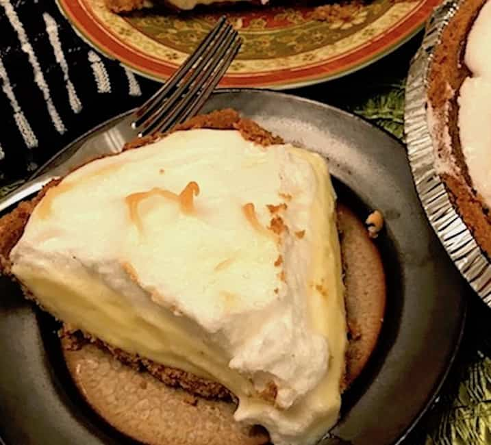 Slice of lemon meringue pie on a plate with a fork