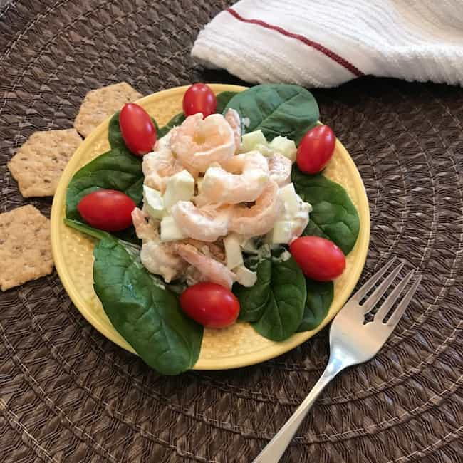 Creamy shrimp salad on a plate with spinach leaves and tomatoes