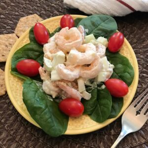 Shrimp salad on a bed of spinach leaves with tomatoes