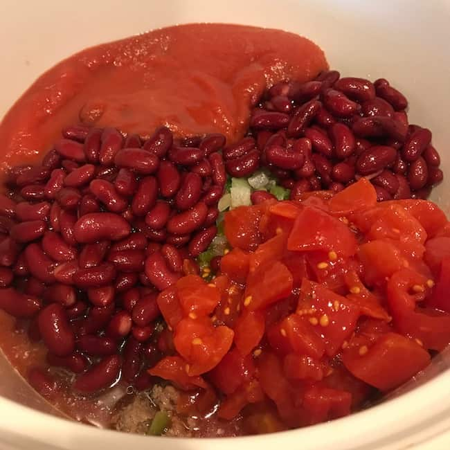 Diced tomatoes and tomato sauce added to the slow cooker to make chili con carne