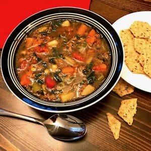 Bowl of homemade vegetable soup beside plate of crackers