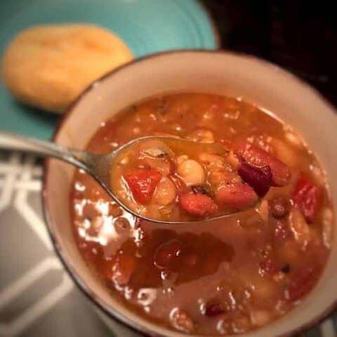 Bowl of 15-bean soup beside a dinner roll