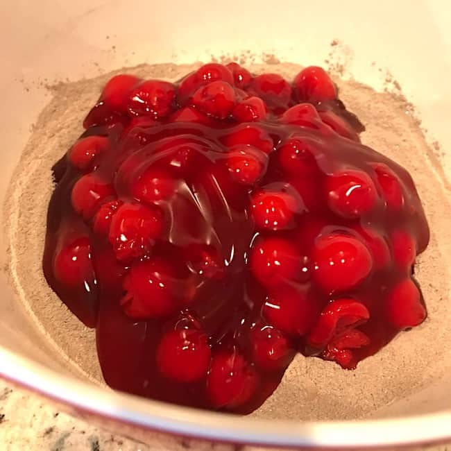 Cake mix and cherry pie filling in a mixing bowl