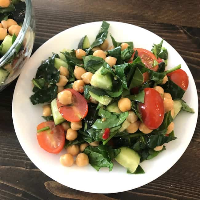 Chickpea salad with tomatoes, cucumbers, and spinach on a plate