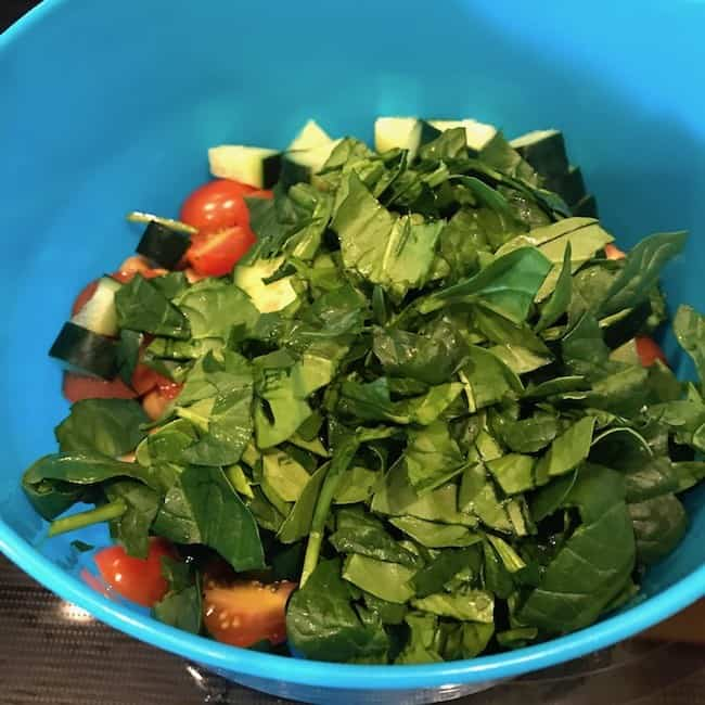 Chopped spinach added to the other ingredients of the chickpea salad