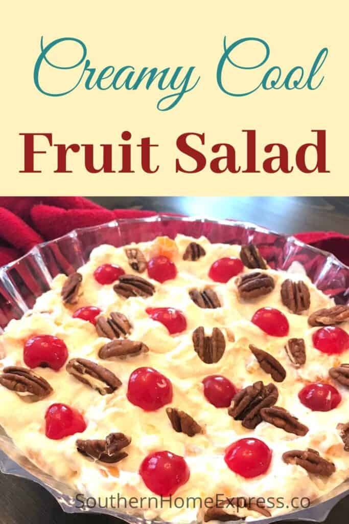 Bowl of creamy cool fruit salad topped with pecans and maraschino cherries.