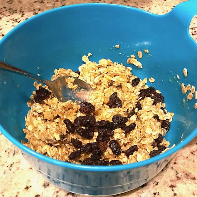 Raisins added to mashed bananas and oatmeal in a bowl
