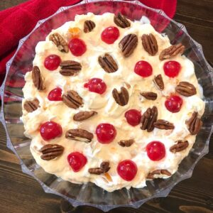 Bowl of creamy fruit salad topped with pecans and cherries