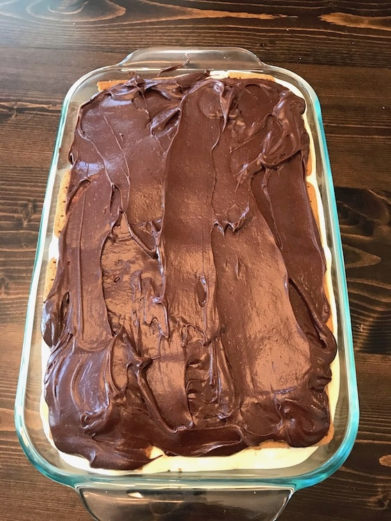 Chocolate frosting spread over top layer of graham crackers