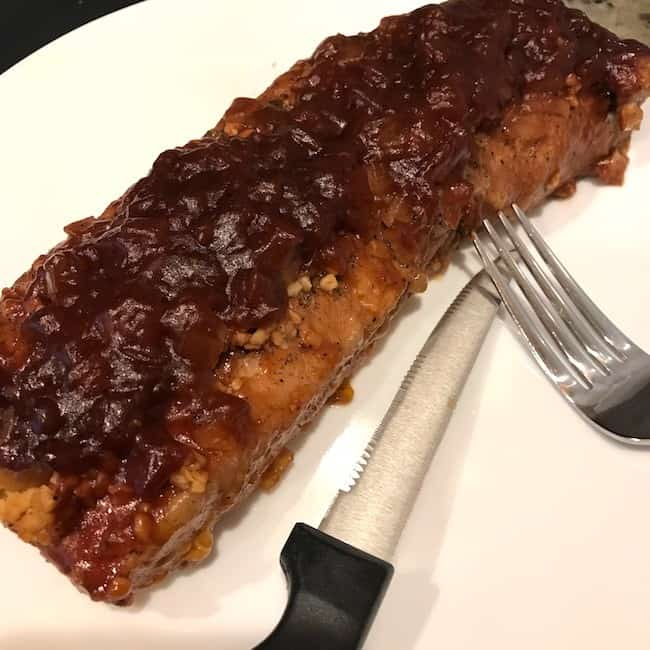Barbecued pork tenderloin resting on a plate beside a fork and knife