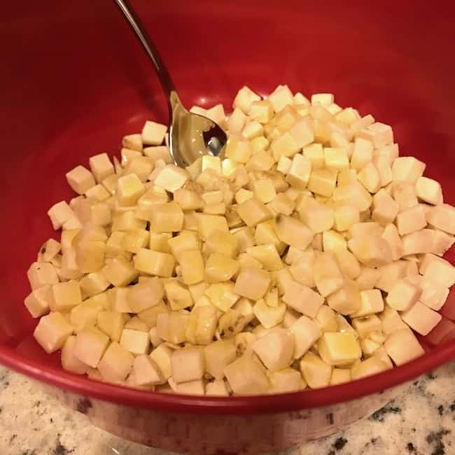 Mixing hash browns with olive oil