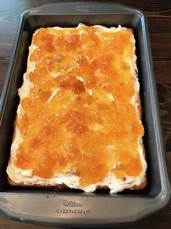 Peach preserves on top of a frosted peach cake