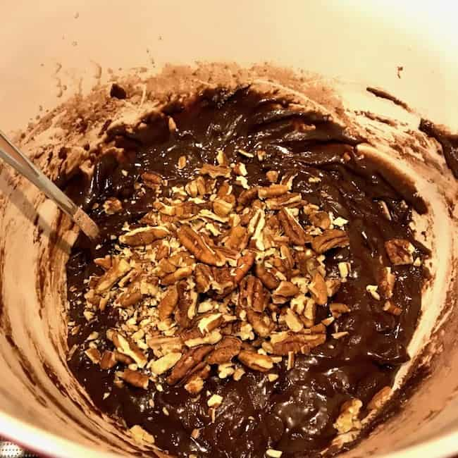 Batter in a bowl with added ingredients including chopped pecans