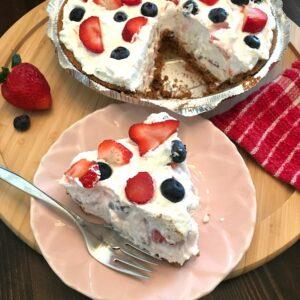 Slice of berry cheesecake beside the full cake