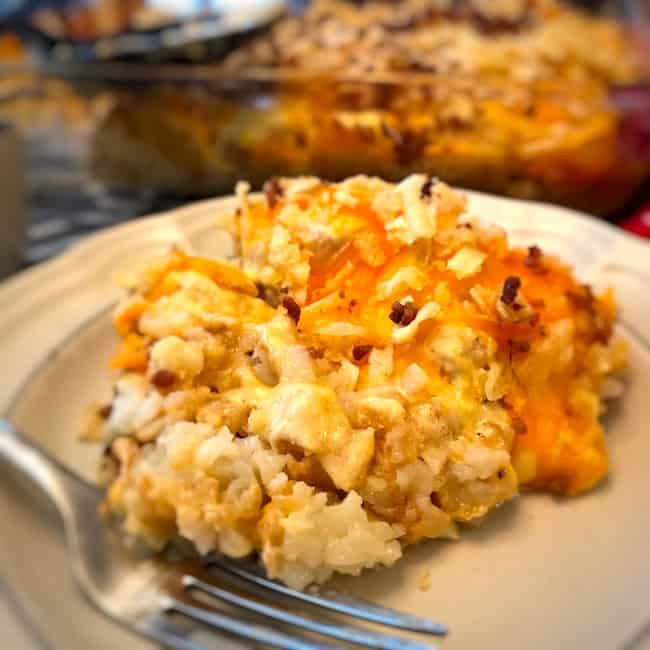 Serving of creamy cheesy Tater Tot casserole on a plate