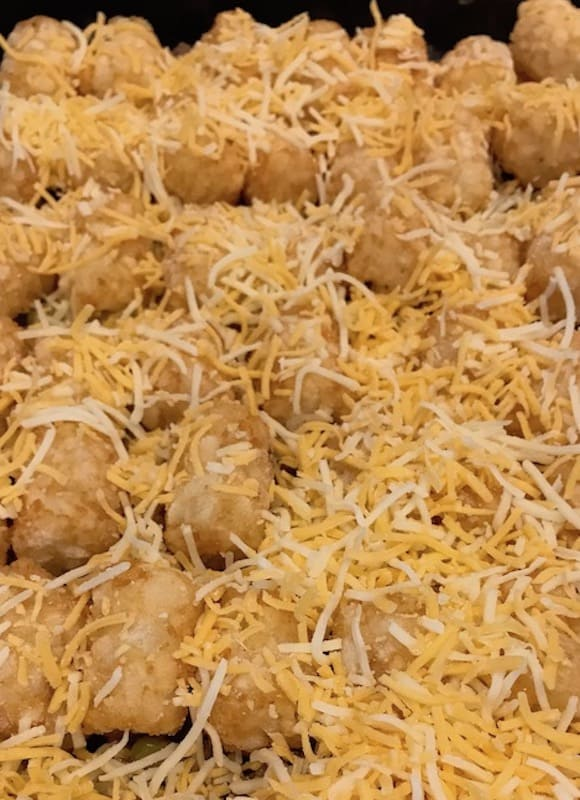 Hamburger Tater Tot casserole with shredded cheese on top