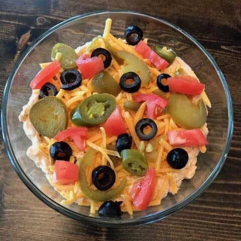 Bowl of taco dip topped with olives, jalapenos, cheese, and tomatoes