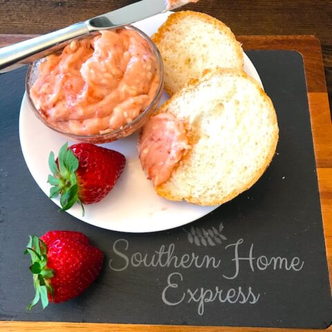 Strawberry butter, bread, and strawberries on a plate