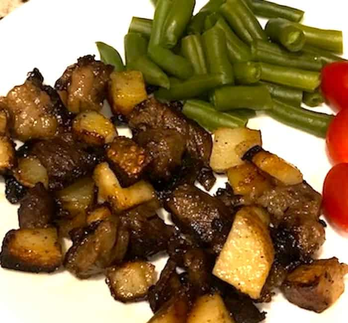 Beef hash on a plate with green beans and tomatoes