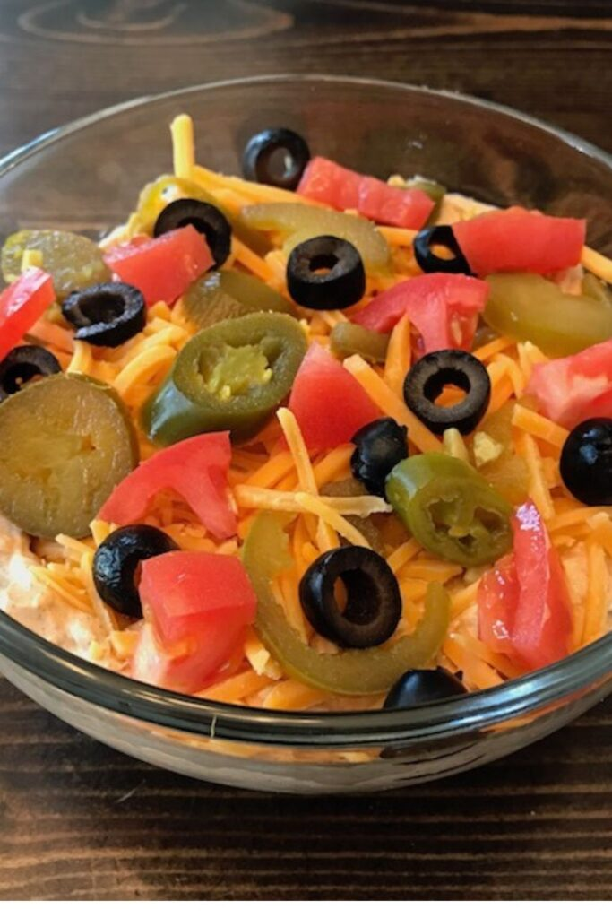 Bowl of taco dip topped with cheese, tomatoes, black olives, and jalapeno slices