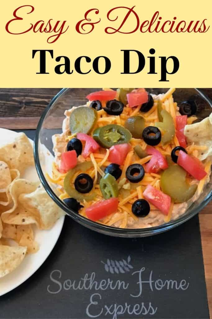 Bowl of taco dip topped with cheese, peppers, black olives, and tomatoes beside a plate of chips