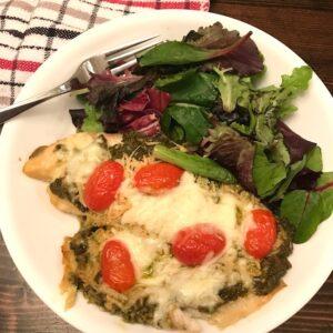 Plate with pesto tilapia and salad