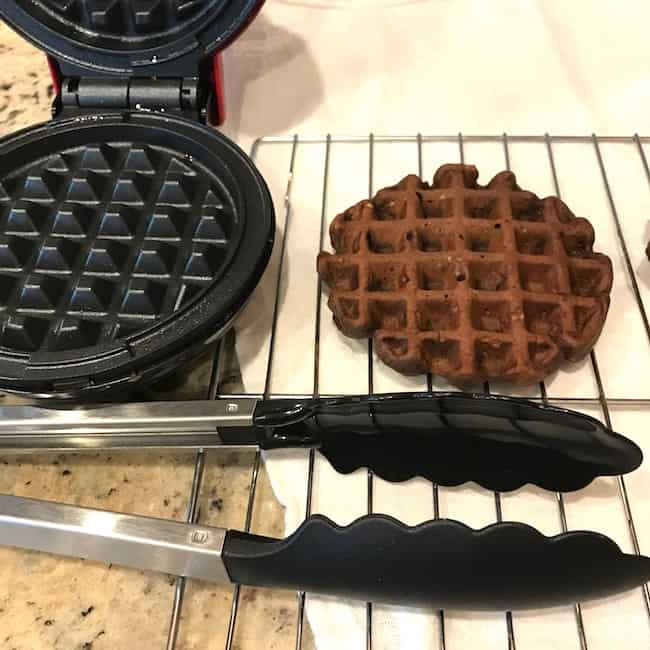 Chocolate cream cheese chaffle on a cooling rack beside the waffle maker and tongs