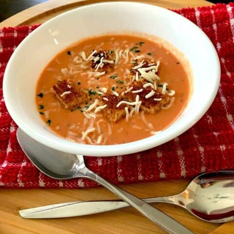 Cream of tomato soup with croutons and shredded cheese on top