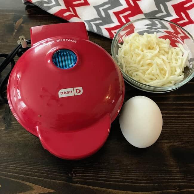 Dash mini waffle maker, shredded cheese, and an egg
