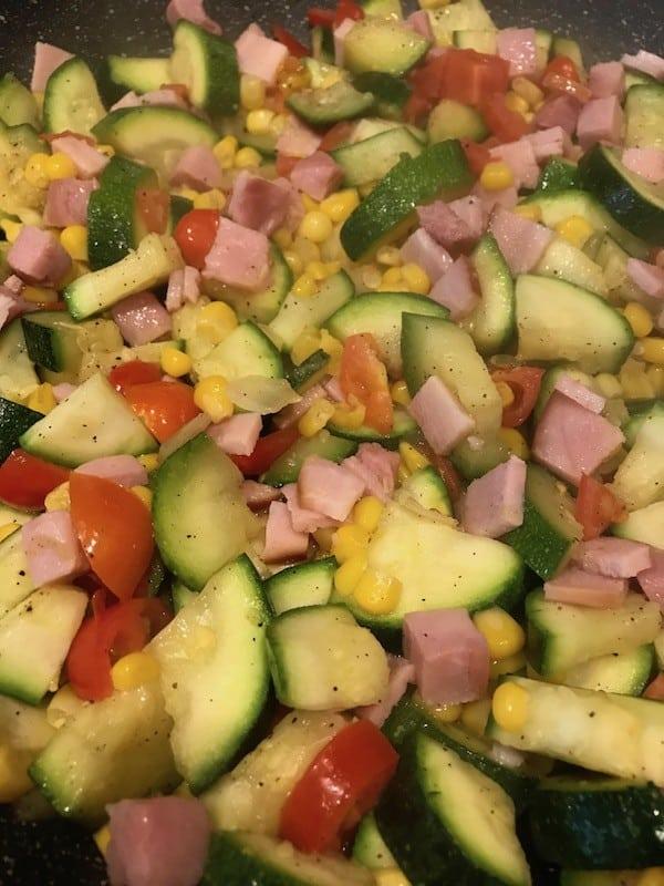 Zucchini, ham, corn, and tomatoes in a casserole for the zucchini bake.