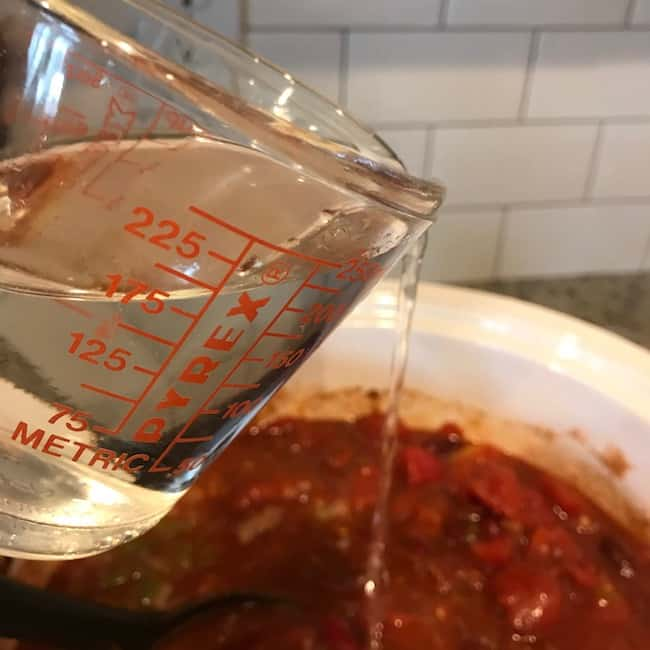Cup of water over pot of chili