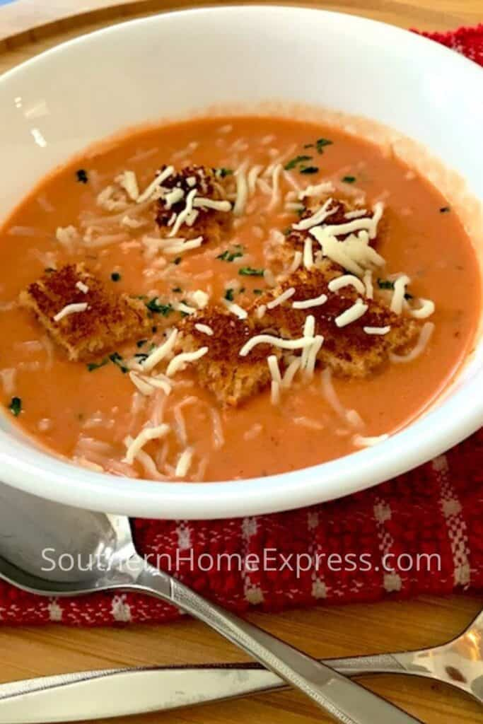 Bowl of cream of tomato soup with crotons and shredded cheese