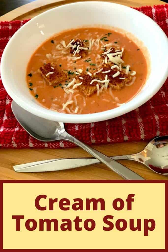 Bowl of cream of tomato soup with croutons and shredded cheese