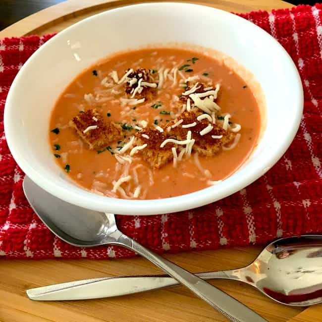 Cream of tomato soup with croutons and cheese