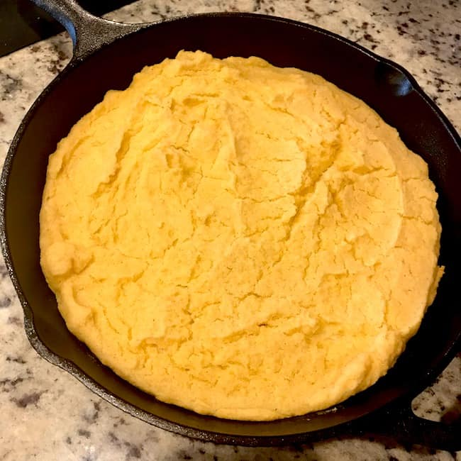 Cooked fine-ground cornmeal cornbread in a skillet