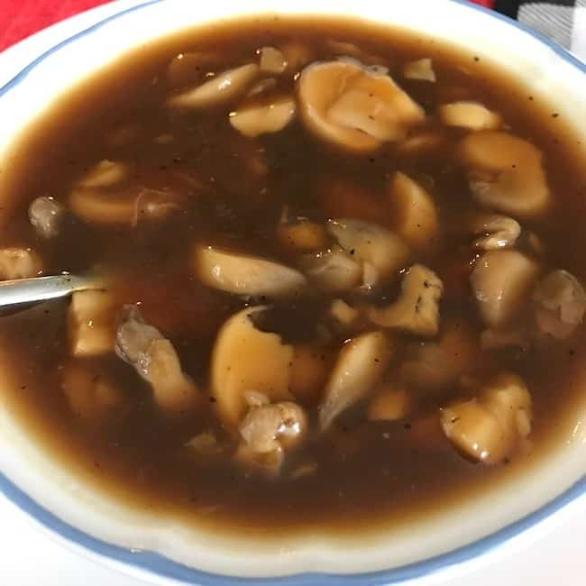 Bowl of gravy with mushrooms
