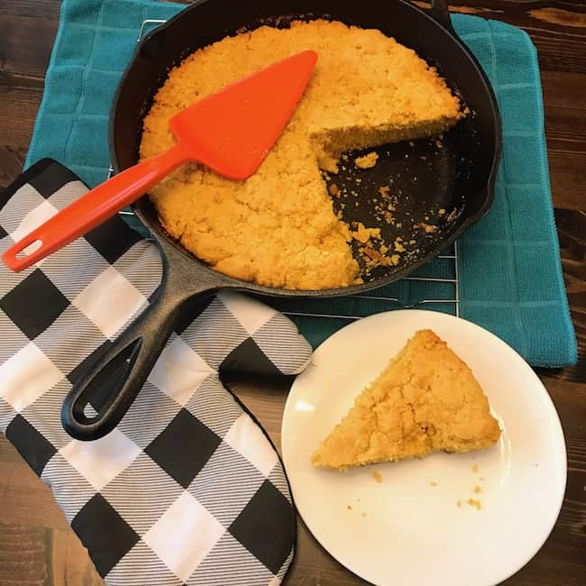 Slice of cornbread on a plate beside a skillet of southern style cornbread