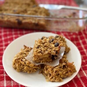 Apple raisin oat bars on a plate in front of a pan