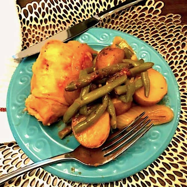 Chicken and vegetables on a plate with a knife and fork