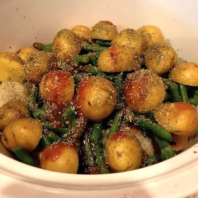 Tomato sauce and seasoning over potatoes and green beans in crockpot