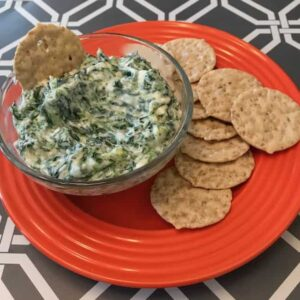 Bowl of spinach dip beside crackers on an orange plate