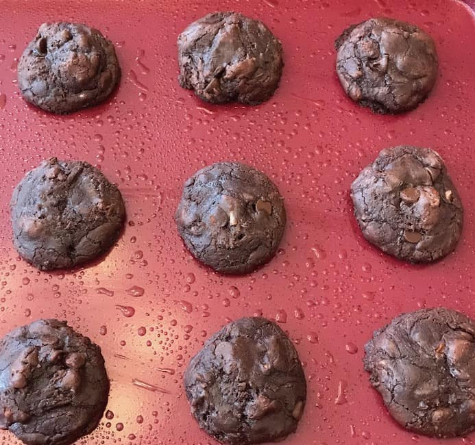 Baked pecan brownie cookies on a cookie sheet