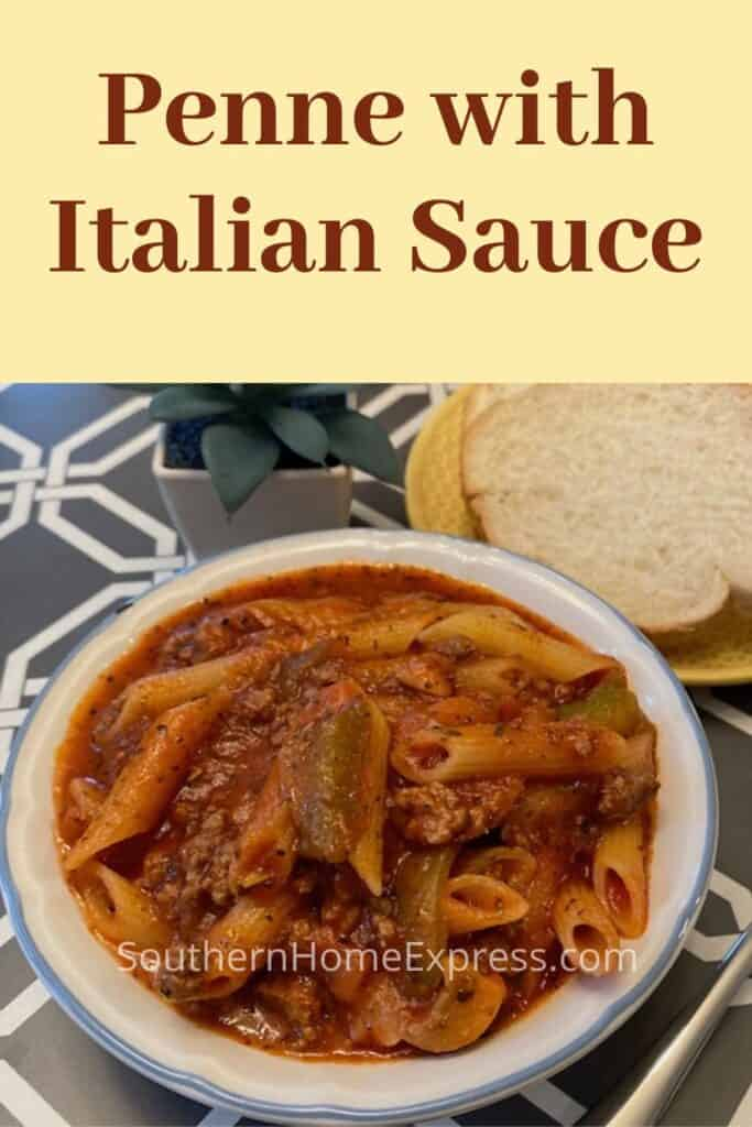 Bowl of Italian pasta with meat sauce beside a slice of bread
