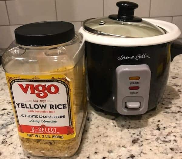 Container of yellow rice and a rice cooker