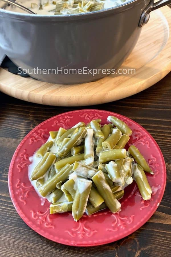 Plate of cheesy green beans beside a pot of green beans