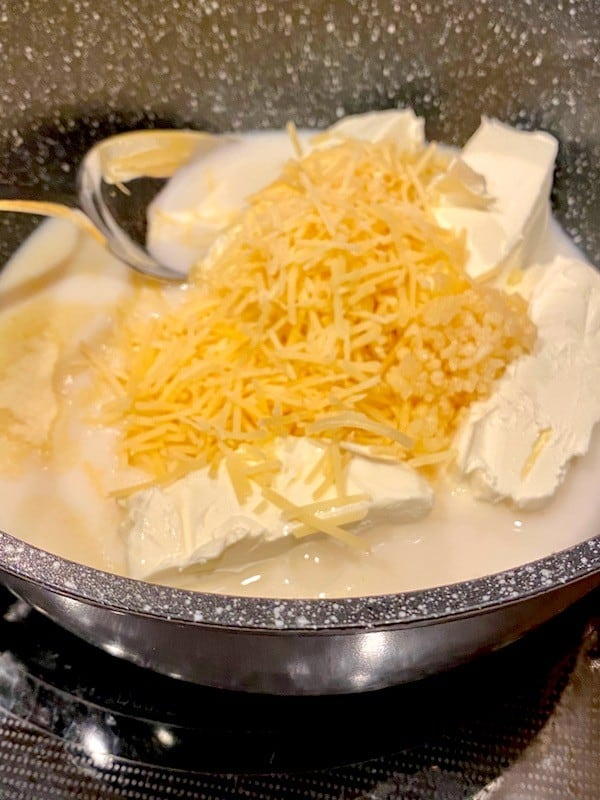 Milk, cream cheese, Parmesan cheese, minced garlic, and onion powder in a pot
