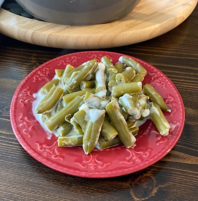 Serving of cheesy green beans on a plate