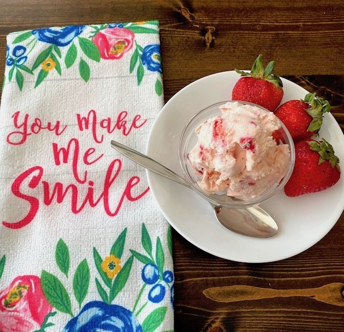 "Bowl of strawberry ice cream, 3 strawberries, and a dish towel that reads, ""You make me smile."""