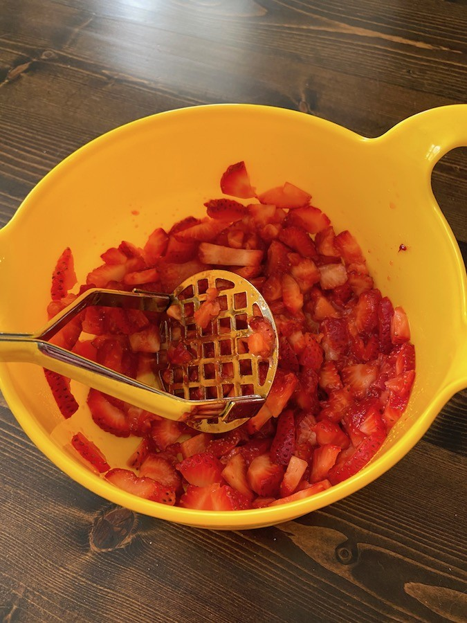Mashing strawberries in a bowl with a potato masher